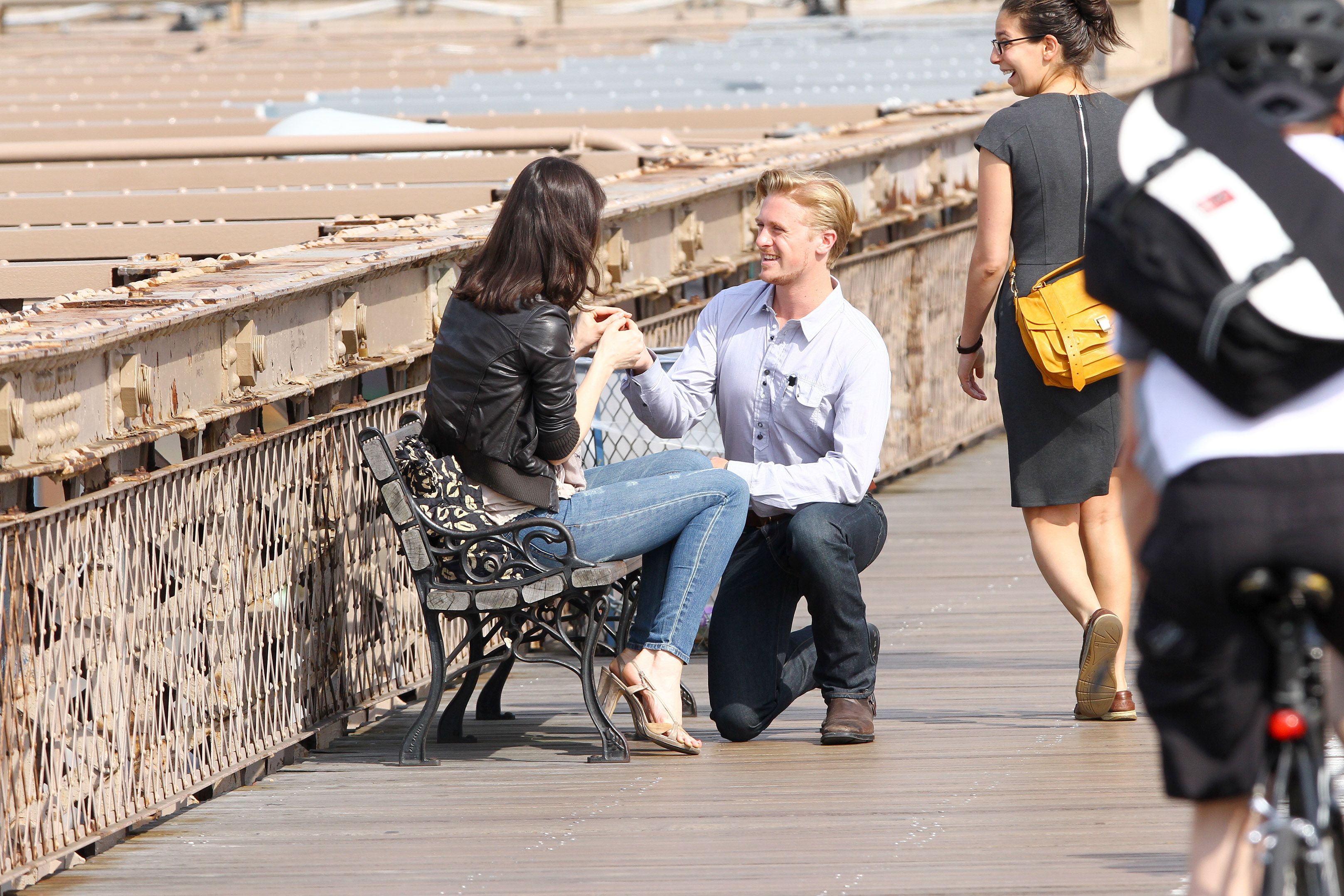 Groom popping question on pier