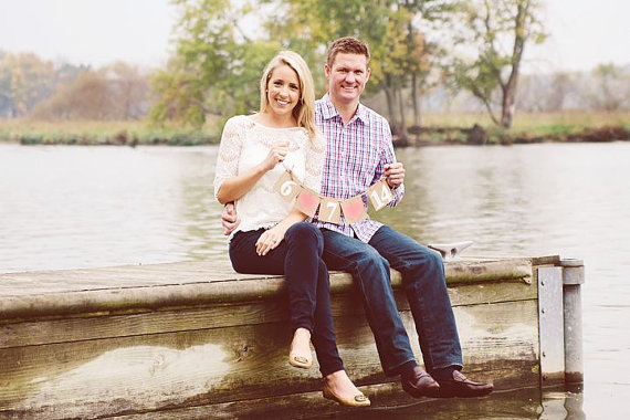 Young engaged couple poses for engagement photo on the dock of a lake