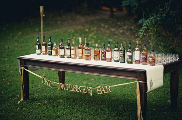 a whiskey bar is set up for a wedding reception