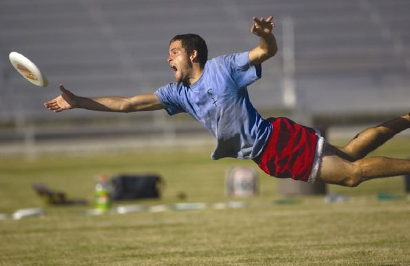 guys dives to catch a frisbee during a game of ultimate